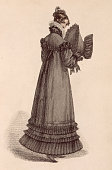 A lady wears a grey highnecked walking dress with a heavilt tiered hem and matching bonnet