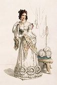 A lady wears an early 19th century dress with a low neckline and decorated hem accompanied with long gloves and an ornate shawl Real flowers adorn...