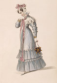 A lady wears an early 19th century waisted walking dress with a ruff collar and a tiered hem A lacy bonnet with a pink bow adorns her head and she...