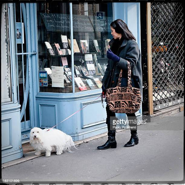 CONTENT] A lady with a dog in front of a library in Paris