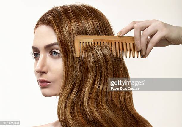 Lady with her red hair being combed
