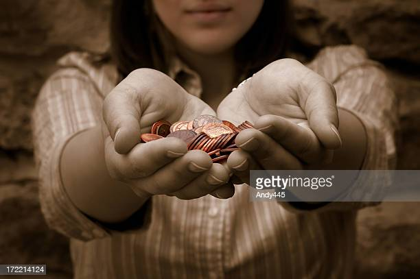 Lady with outstretched hands holding lots of penny coins