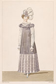 A lady's Empireline grey linen day dress with a checked hem and a plumed hat