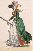 A lady's Germanstyle riding outfit The rider carries a riding crop and a large decorated hat