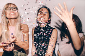 Photo of a group of young women celebrating their youth, femininity  and friendship - tossing a confetti in the air while dancing