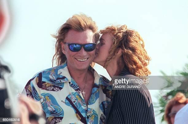 Laeticia épouse du chanteur de rock et acteur français Johnny Hallyday embrasse son mari le 22 juin 1996 au Cap d'Agde où ils passent leurs vacances...