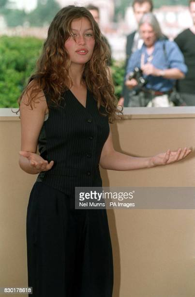 Laetitia Casta gestures during a photocall for L'oreal products on the rooftop of the Palais des Festivals at the 1999 Cannes Film Festival in France