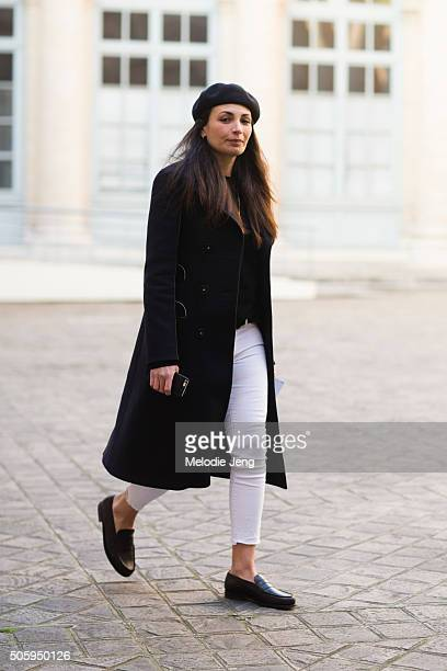 Laetitia Paul GQ France Fashion Editor wears a black beret a long black coat cropped white jeans and loafers on January 20 2016 in Paris France