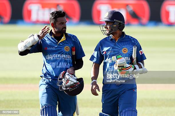 Lahiru Thirimanne and Dinesh Chandimal both of Sri Lanka walk from the field after winning the third One Day International match between New Zealand...