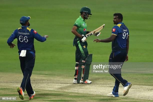 Lahiru Thirimanne and Lahiru Gamage of Sri Lanka celebartes the wicket of Babar Azam of Pakistan during the third One Day International match between...