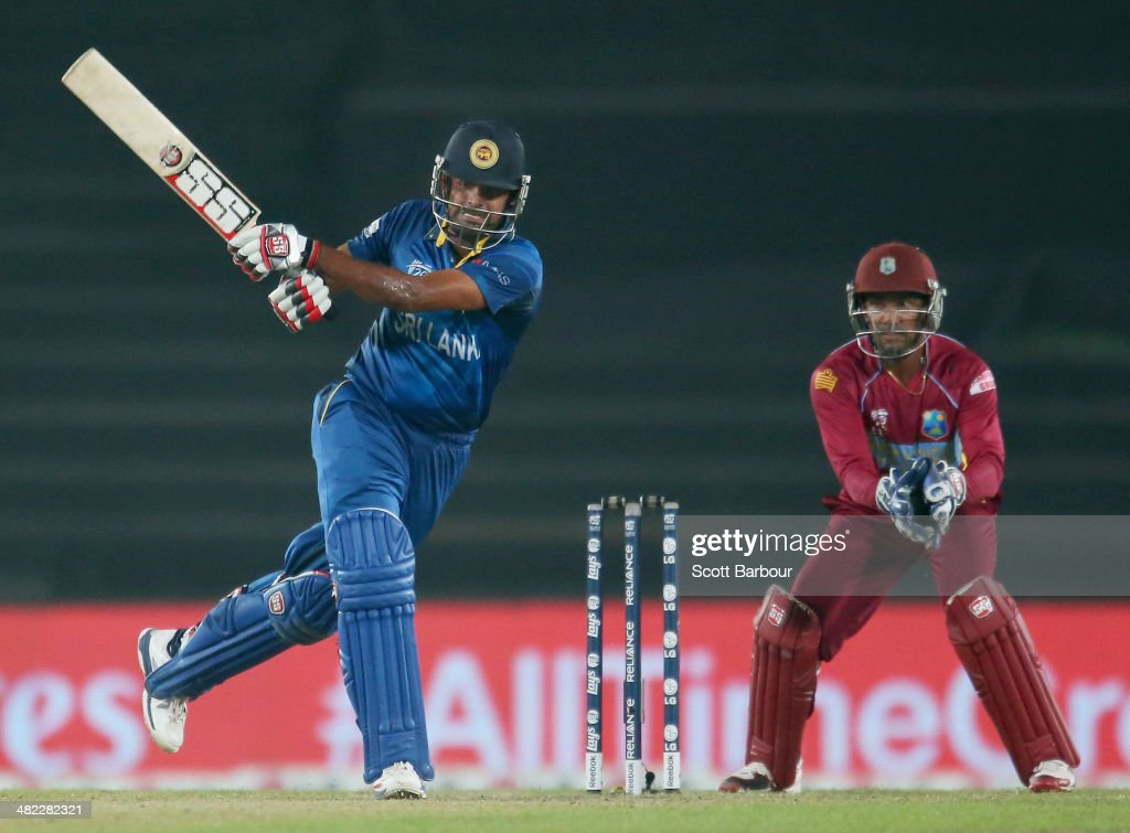 Lahiru Thirimanne of Sri Lanka bats as Denesh Ramdin of the West Indies looks on during the ICC World Twenty20 Bangladesh 2014 1st Semi-Final match between Sri Lanka and the West Indies at Sher-e-Bangla Mirpur Stadium on April 3, 2014 in Dhaka, Bangladesh.