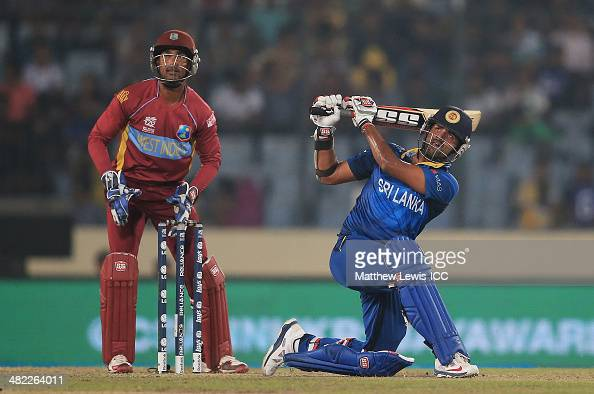Lahiru Thirimanne of Sri Lanka hits a six as Denesh Ramdin of the West Indies looks on during the ICC World Twenty20 Bangladesh 2014 Semi Final match...