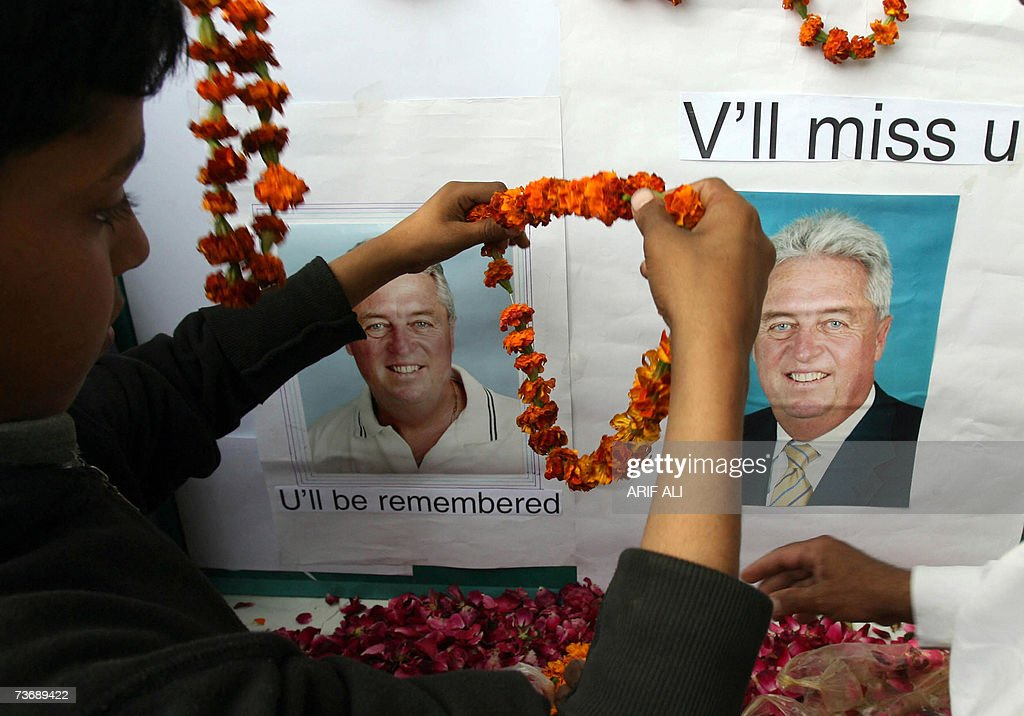 A Pakistani cricket supporter places floral garlands onto pictures of late Pakistani coach Bob Woolmer during a condolance ceremony in Lahore, 24 March 2007. Pakistan's cricketers, shaken by the murder of coach Bob Woolmer, which followed their ignominious World Cup exit, were to head home as Jamaican police hunted for clues about the killing. AFP PHOTO/Arif ALI