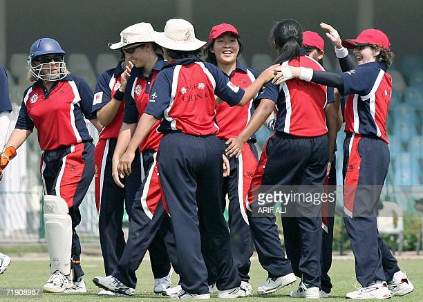 Hong Kong women cricketers celebrate the dismissal of unseen Pakistani batswoman Sajada Shah during the first match of a three match series against...