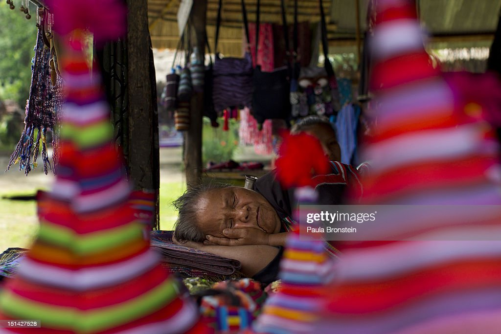 A Lahu hill tribe elderly woman sleeps during a slow day without tourists at the Baan Tong Luang village on September 4, 2012 in Maerim, Thailand. Baan Tong Luang is a fabricated village containing 6 separate Thai Hill Tribes where visitors are expected to pay $16 or 500 Thai bhat for the entrance fee. The ethnic tribes include the Lahu, Hmong, White Karen, Long necked Karen, Yao, Akha. The village opened since 2005 attempts to preserve the old traditions of the ethnic Hill Tribe, also providing an income for them. Life for many of Thailand's Hill Tribe population can be difficult since it can be hard for them to make a living. Their language, costume and culture are different along with the frequent legal problems over Thai citizenship. Hill tribe is a term used in Thailand for all of the various tribal peoples who migrated from Tibet, or elsewhere in China over the past few centuries.