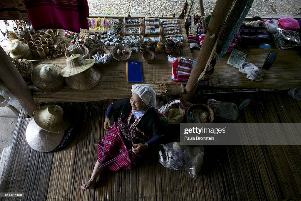 A Lahu hill tribe woman creates more handicrafts for sale at the Baan Tong Luang village on September 4, 2012 in Maerim, Thailand. Baan Tong Luang is a fabricated village containing 6 separate Thai Hill Tribes where visitors are expected to pay $16 or 500 Thai bhat for the entrance fee. The ethnic tribes include the Lahu, Hmong, White Karen, Long necked Karen, Yao, Akha. The village opened since 2005 attempts to preserve the old traditions of the ethnic Hill Tribe, also providing an income for them. Life for many of Thailand's Hill Tribe population can be difficult since it can be hard for them to make a living. Their language, costume and culture are different along with the frequent legal problems over Thai citizenship. Hill tribe is a term used in Thailand for all of the various tribal peoples who migrated from Tibet, or elsewhere in China over the past few centuries.