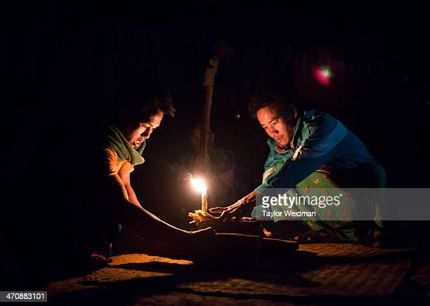 Lahu men light a beeswax candle to begin an evening's dancing during the New Year celebrations The Lahu people celebrate their New Year or Kho Jouw...