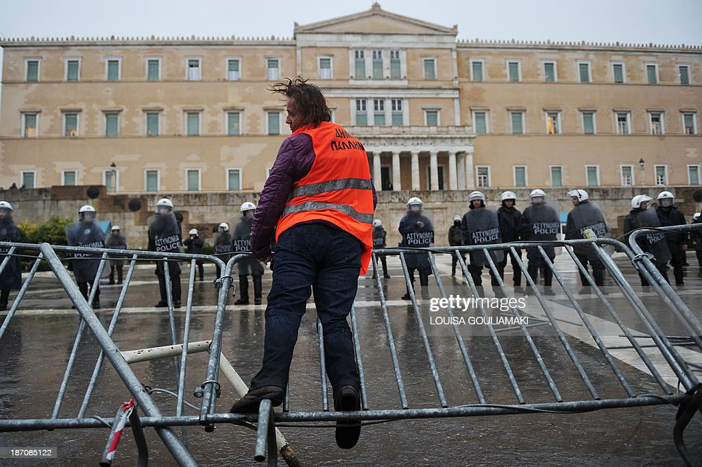 A laid off school guard jumps over a barrier protecting the Greek Parliament in Athens on November 6, 2013 during a protest as part of a 24-hour strike. A general strike hit Greece on November 6, paralyzing public services and disrupting transport as EU-IMF auditors worked to finalize the recession-hit country's next budget, looking to eliminate a fiscal shortfall that could bring more unpopular cuts. AFP PHOTO / LOUISA GOULIAMAKI