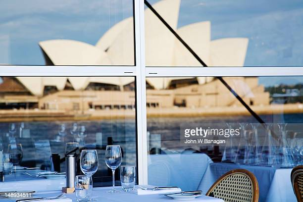 Laid table of a restaurant with Opera House in background.
