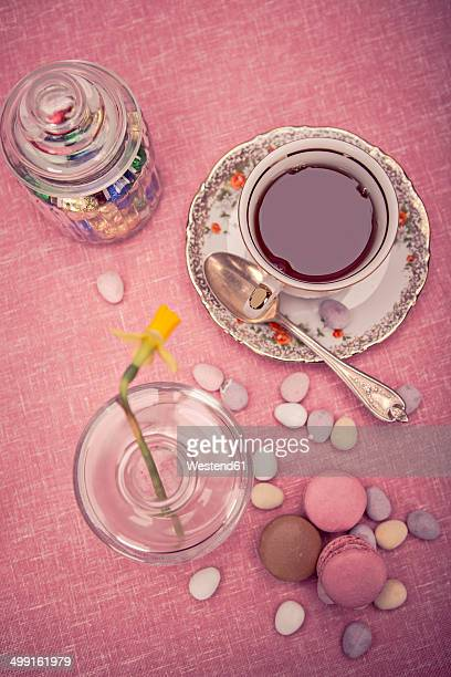 Laid table with cup of tea, daffodil (Narcissus pseudonarcissus), macarons and a glass of sweets, elevated view