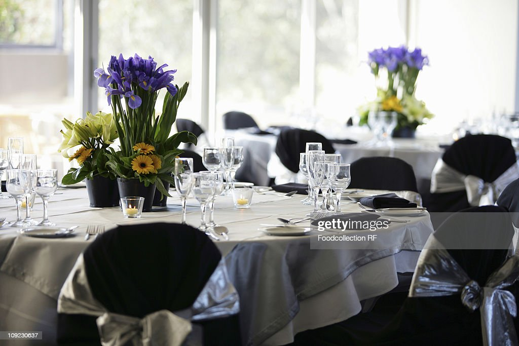 Laid tables with floral decorations in restaurant : Stock Photo