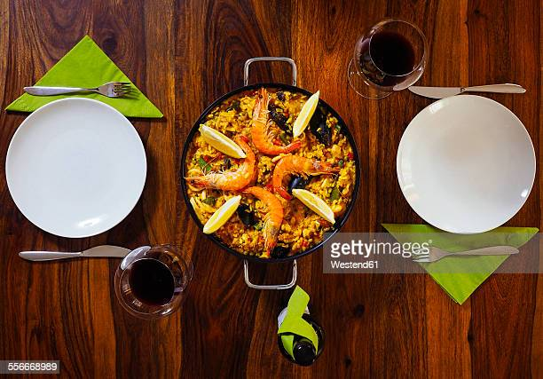 Laid wood table with fresh paella and red wine