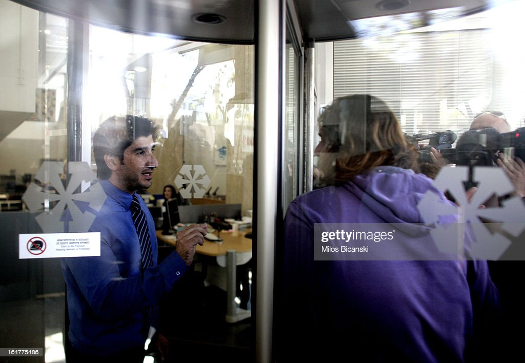 A Laiki (Popula) Bank employee speaks to a customer as they both stand in a revolving door, as the country's banks re-open following 12 days of closure on March 28, 2013 in Nicosia, Cyprus. Bank trading began again after the government negotiated a EUR 10bn (GBP 8.4bn) bailout package. Captial controls are limiting withdrawals to EUR 300 perday and the Cyprus stock excahnge remains closed.