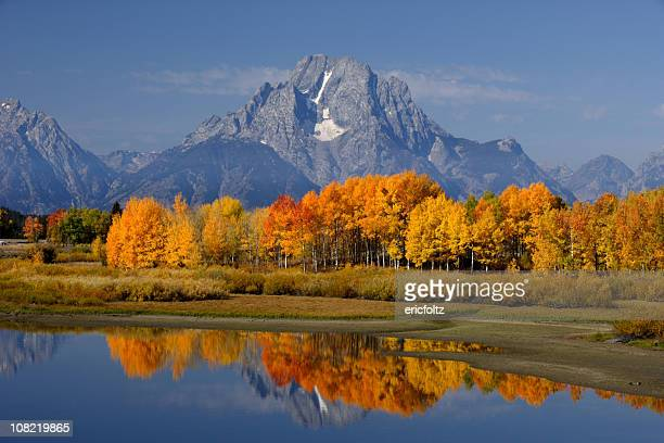 Lake and Autumn Forest Against Mountains