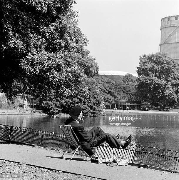 Lake Battersea Park London 19621964 An elderly man in suit and beret seated on a foldup chair looking across towards the round cafe and gasometer