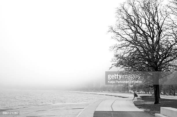 Lake By City During Foggy Weather