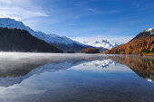 Lake Champfer with larch forest with autumnal colouring, Mt Piz da la Margna at back, St. Moritz, Engadine, Grisons, Switzerland, Europe