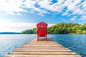 Relaxing by the water is way to spend a summer afternoon.  A cottage dock with a red Adirondack chair at the end for someone to relax and look out over the water.  Lake and trees in the background.