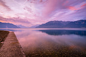 Colourful rays of light hit the clouds above the alps. Lake Geneva in the foreground is calm and peaceful