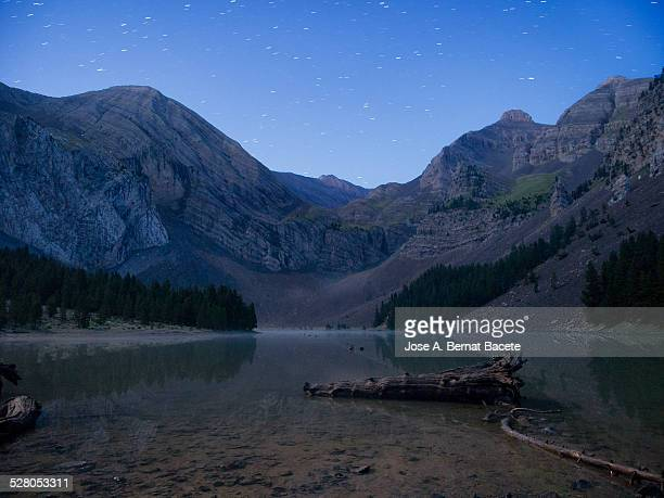 Lake glacier between mountains on a starry night