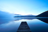A pier stretches out over Lake Kaniere on New Zealand's South Island.
