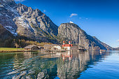Beautiful view of scenic mountain scenery with Lake Konigssee with famous Sankt Bartholomae pilgrimage church and passenger ship, Nationalpark Berchtesgadener Land, Bavaria, Germany