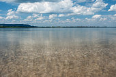 The shallow lakeside of the lake Kochelsee in the Bavarian prealps, on a summer day under blue sky and a few clouds. Photograph taken near Kochelsee, Bavaria, Germany.