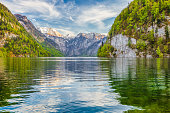 Beautiful view of famous Lake Koenigssee with idyllic mountain scenery and famous Sankt Bartholomae pilgrimage church in the background in springtime, National Park Berchtesgadener Land, Bavaria, Germ