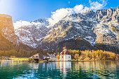 Panoramic view of scenic mountain scenery with Lake Konigssee with world famous Sankt Bartholomae (St. Bartholomew) pilgrimage church in fall, Nationalpark Berchtesgadener Land, Bavaria, Germany.