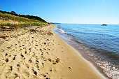 Sandy shore of Lake Michigan at Saugatuck Dunes State Park in Allegan County, Michigan. Distant people and moored boat.