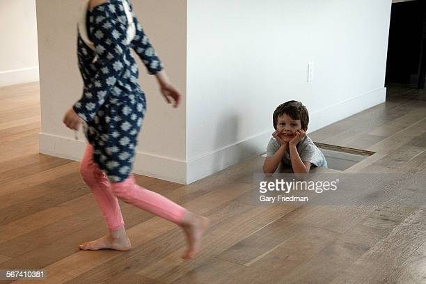 Lake Murname peeks out from a climbing wall from his bedroom as his sister Emerson walks by in the home of their parents McShane and Cleo Murnane on...