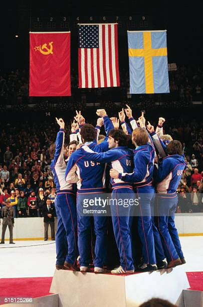 The American Olympic Hockey Team crowds onto the center podium with fingers pointed skyward designating their 'Number One' status at Olympic awards...