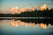 Trees and clouds reflected on calm water on a pristine lake.