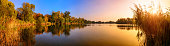 Panorama of a gorgeous sunset at a lake, with gold and blue color and trees reflected in the water