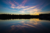 A swedish lake just after sunset, with beautiful patterns in the sky. Both the sky and the tree line far away at the opposite side of the lake are reflected in the water.