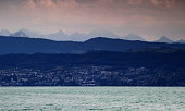 On the shore of Lake Zurich the suburb Horgen with green hills, mountains and jagged Glarner Alps in the background, Switzerland, Europe