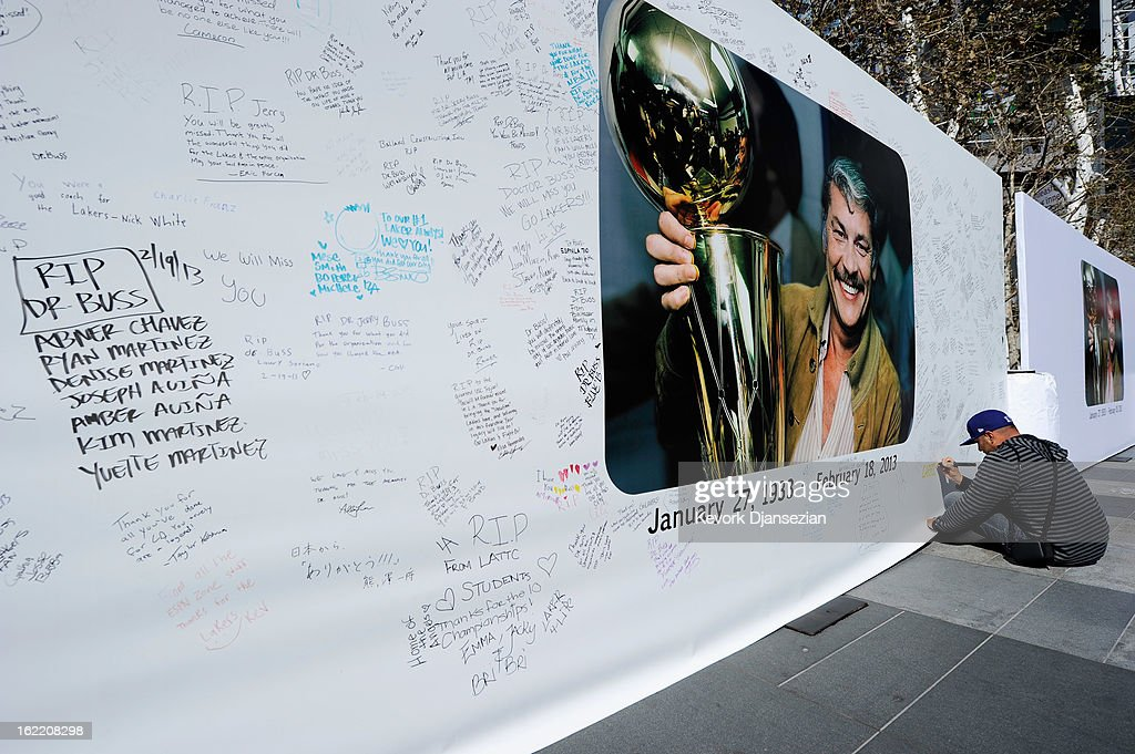 Lakers fan Paul Carillo writes a personal message on the Dr. Buss Memorial Banners in the Nokia Plaza at L.A. Live, directly across the street from Staples Center on February 20, 2013 in Los Angeles, California. The Lakers will hold a memorial service to celebrate the life of longtime owner Jerry Buss at the Nokia Theater on Thursday, for invited guests only. Dr. Buss died at the age of 80 on Monday following an 18-month battle with cancer.