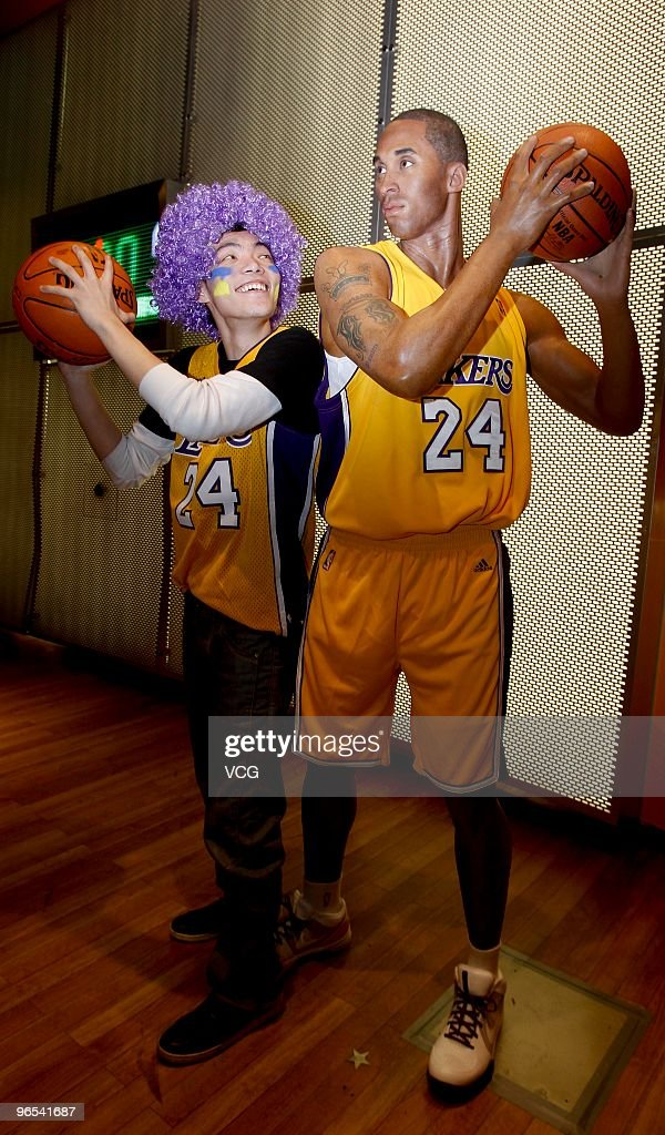 A Lakers fan poses for photos with the waxwork of American shooting guard Kobe Bryant at Madame Tussauds on February 9 2010 in Shanghai of China
