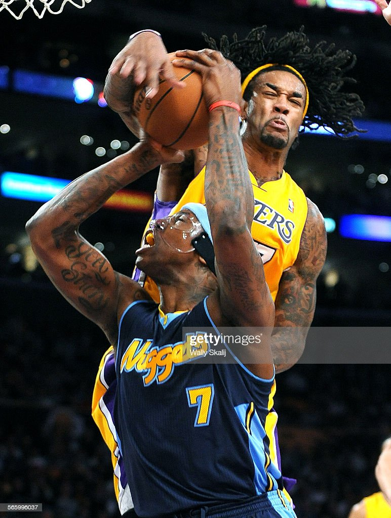 Lakers Jordan Hill blocks the shot of Nug s Al Harrington but is