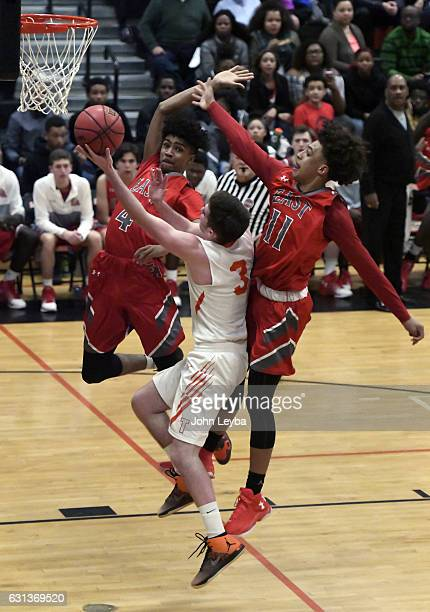Lakewood Tigers Kolton Peterson goes up for a a shot on East Angels Ja'Shawn Chisel and East Angels Kwane Marble during their game January 9 2017 at...